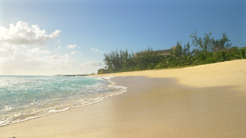 SLOW MOTION, LOW ANGLE: Idyllic shot of the crystal clear sea waves sweeping over the sandy shore in Barbados. Glassy waves wash the white sand beach near a oceanfront hotel in the sunny Caribbean.