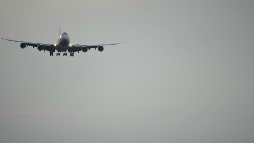 4K footage of a 4 engine jumbo jet plane landing. Jet airplane descending before landing in airport at cloudy morning