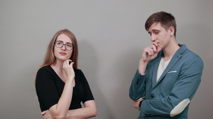 Hand on chin thinking about question, pensive expression. Doubt. Thoughtful face. Using that incredibly sharp business mind. Young attractive couple boyfriend girlfriend, two people
