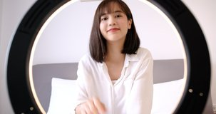 Beautiful Asian woman vlogger recording dressing up of clothes hanging on a hanger in the wardrobe, Modern businesswoman using social media for marketing.