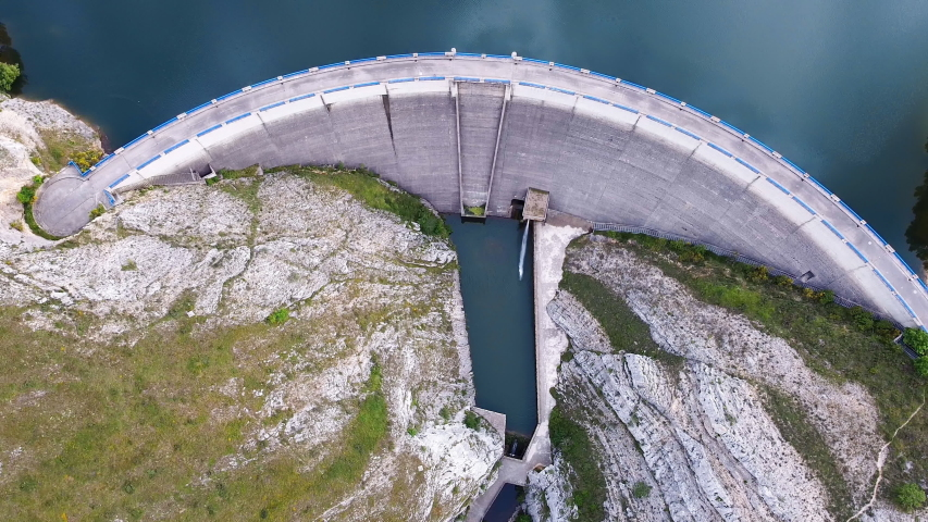Aerial drone footage top view Water dam and reservoir lake, generating hydro electricity power renewable energy and sustainable development. . High quality 4k footage Royalty-Free Stock Footage #1054394669