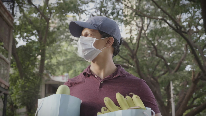 A movement shot of a delivery man/ boy wearing protective face mask carrying groceries/ fruits/ vegetables walking outdoors on the street/ road amid corona virus or COVID 19 epidemic or pandemic
