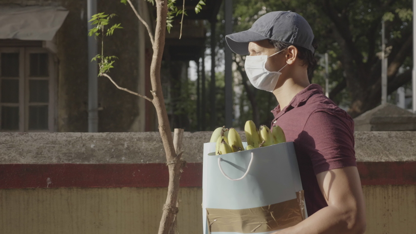 A delivery man/ boy wearing protective face mask and cap carrying groceries/ fruits/ vegetables walking outdoors on the street/ road amid corona virus or COVID 19 epidemic or pandemic