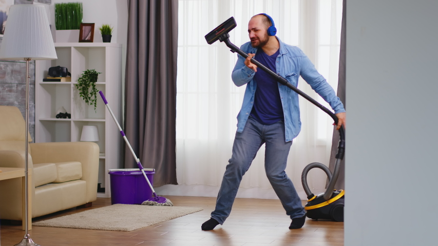 Funny young man listening music on headphone while cleaning the floor with vacuum cleaner. Happy dancing singing couple cleaning apartment, household and housekeeping, vaccum and mop, clean-up the hou Royalty-Free Stock Footage #1054398035