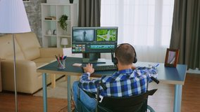 Invalid man in wheelchair editing a video using post production software wearing headphones. Handicapped invalid paralysed freelancer, immobilized entrepreneur working from home, ilness and disability