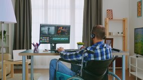 Handicapped video editor in wheelchair working from home wearing headphones. Handicapped invalid paralysed freelancer, immobilized entrepreneur working from home, ilness and disability
