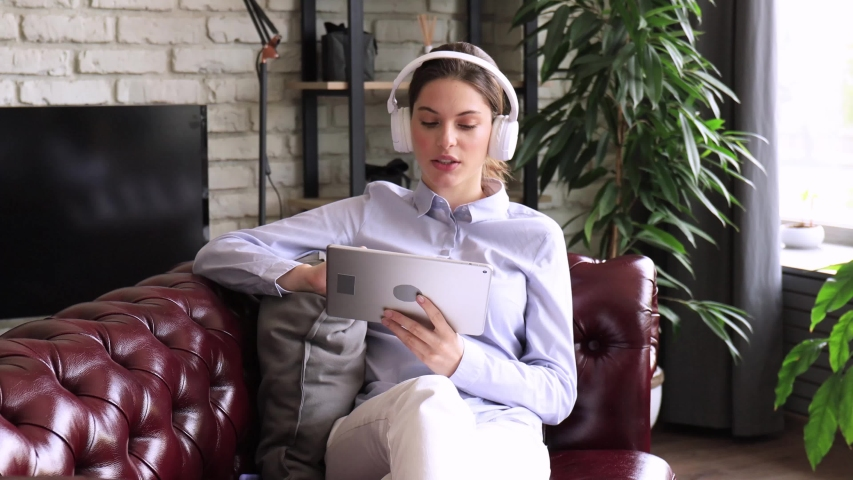 Young attractive smiling caucasian woman using tablet sitting on sofa at home, singing song, enjoying free time. Girl student studying design apps on digital touchpad.