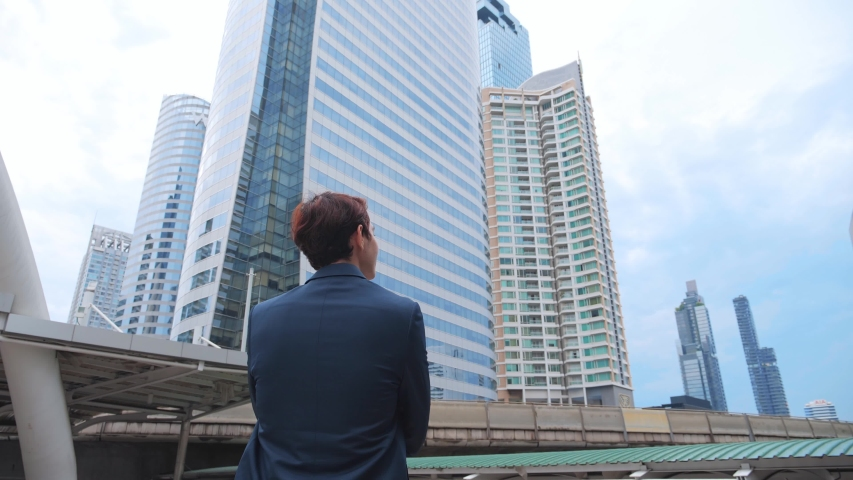Back view of the Thoughtful Businessman wearing a Suit looking out while standing near modern Office Building background. 4K Slow Motion Corporate. Royalty-Free Stock Footage #1054402961