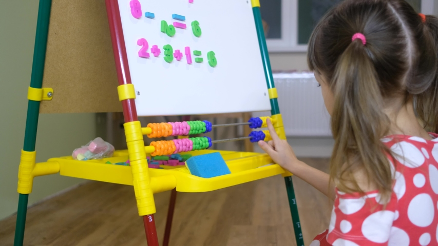 child girl using abacus to learn numbers and account at home