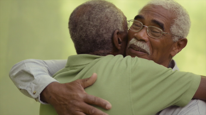 Retired old men and leisure, happy senior black brothers talking and hugging in park. Elderly African american friends embracing, smiling, speaking. Emotional reunion of veterans