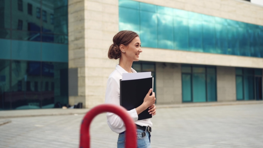 Businesswoman successful woman business person standing outdoor corporate building exterior Pensive elegance cute caucasian confidence professional business woman holding folder documents Bank worker | Shutterstock HD Video #1054406036