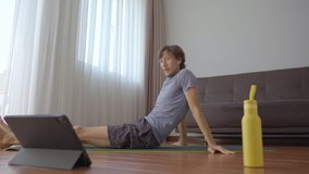 A young man at home doing physical exercises following instructions from a video he watches on a tablet. Social distancing concept. Internet trainer concept