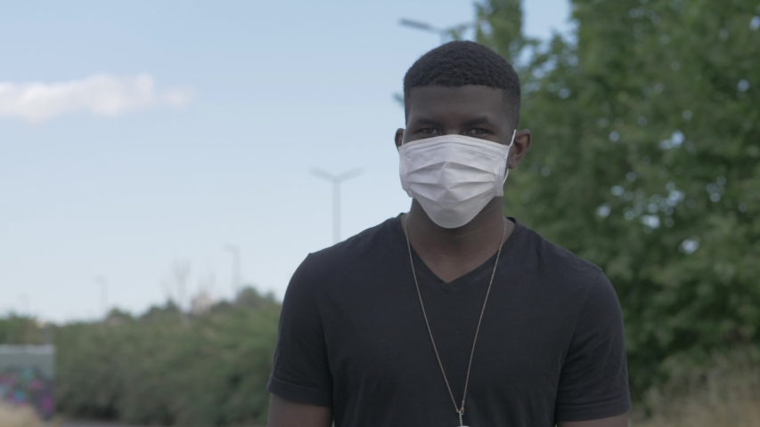 Sequence shot on young african man wearing surgical mask walking staring at camera - outdoors | Shutterstock HD Video #1054406489
