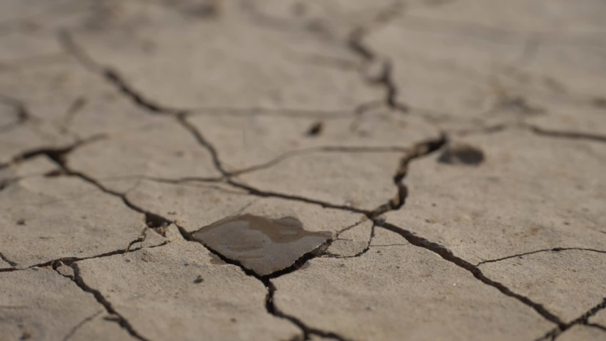 Drought concept - lack of water, climate change and global warming. water drop falling. water splash with dry soil on background. ecology concept, nature landscape. water resource use | Shutterstock HD Video #1054407101