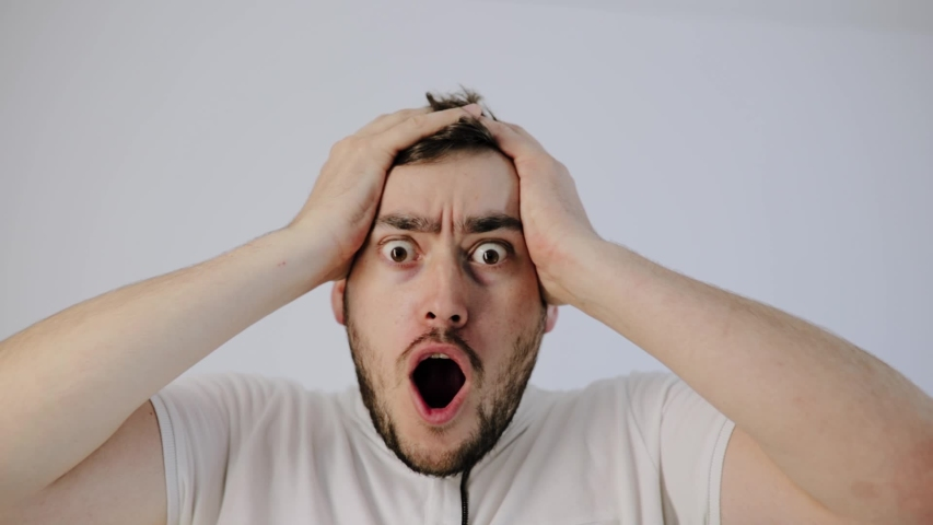 shocked man put hands on head and very surprised puts his hands to his head, People sincere emotions, on white background, studio shot | Shutterstock HD Video #1054407893