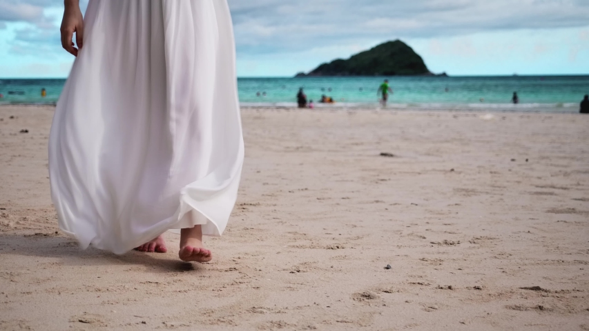 woman walking on sand at the beach close up on feet. woman wear long dress.slow motion footage. Royalty-Free Stock Footage #1054407935