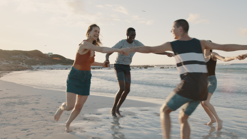 Group of friends playing with holding hands on the beach. Men and woman playing ring around the rosy on the sea shore.