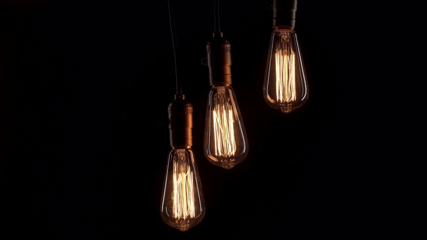 Three retro lamps hang and turn on at the same time on black background. Antique bulbs with old lamp holder are switched on | Shutterstock HD Video #1054408553