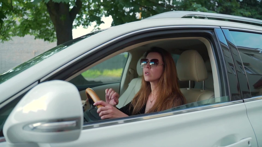 Portrait stylish attractive woman in sunglasses parked in the parking lot behind the wheel of a car. Female goes back. with an open window of a luxury car. Looking in the mirror