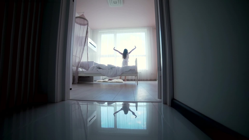 Little teen girl wakes up in the morning in the bedroom gets up comes to the window and pulls his hands up. silhouette child through the door getting out of bed morning. quiet cozy children room
