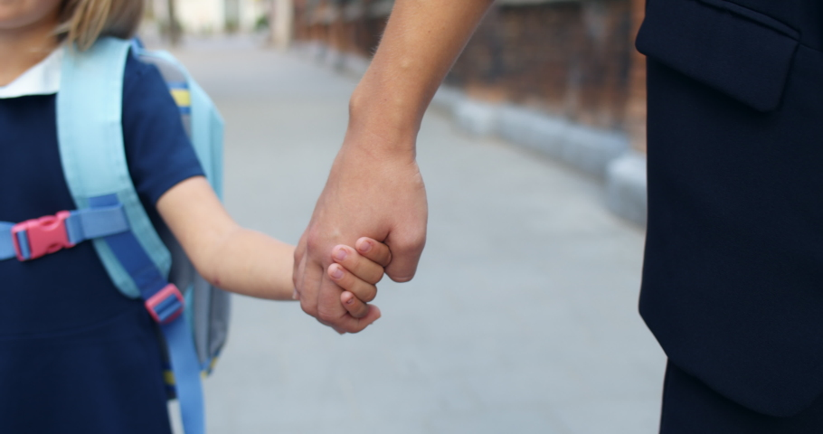 Close up view of mother and daughter walking hand in hand together at street. Mom taking her elementary graded kid to school. Concept of family relationships | Shutterstock HD Video #1054408868