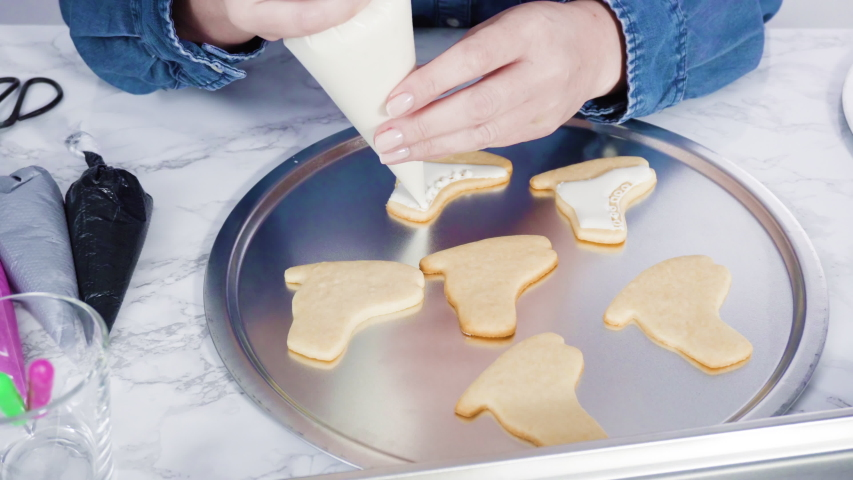 Decorating ice skate shaped sugar cookies with white color royal icing. | Shutterstock HD Video #1054409120
