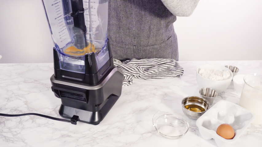 Mixing ingredient in an electric blender to make the crepes batter. | Shutterstock HD Video #1054409369