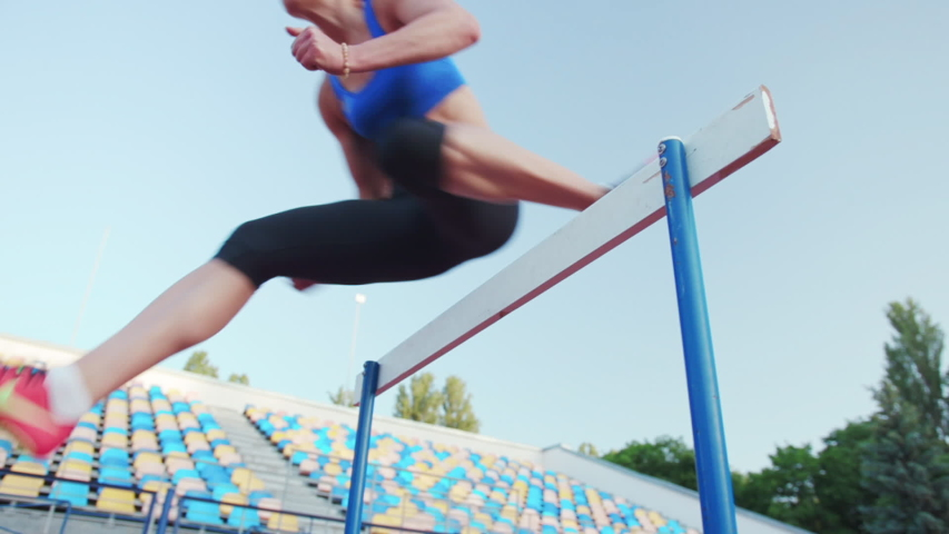 Caucasian female athlete practicing at a sports stadium, hurdling on running track, slow motion. Track and Field Sports Training in Stadium.