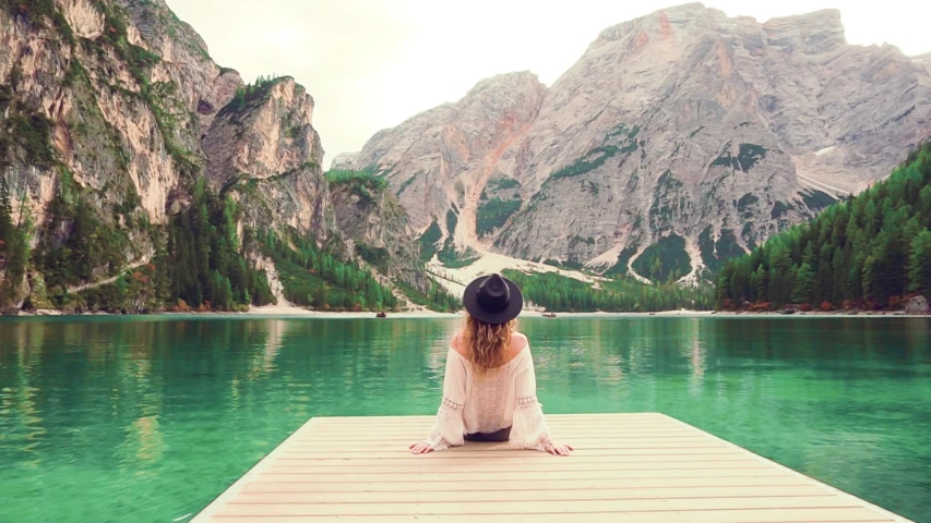 Mysterious woman tourist sits on wooden pier. Amazing view turquoise water high mountain lake Braies mountains. Casual boho style clothing cotton blouse shirt vintage black hat. turned away back view