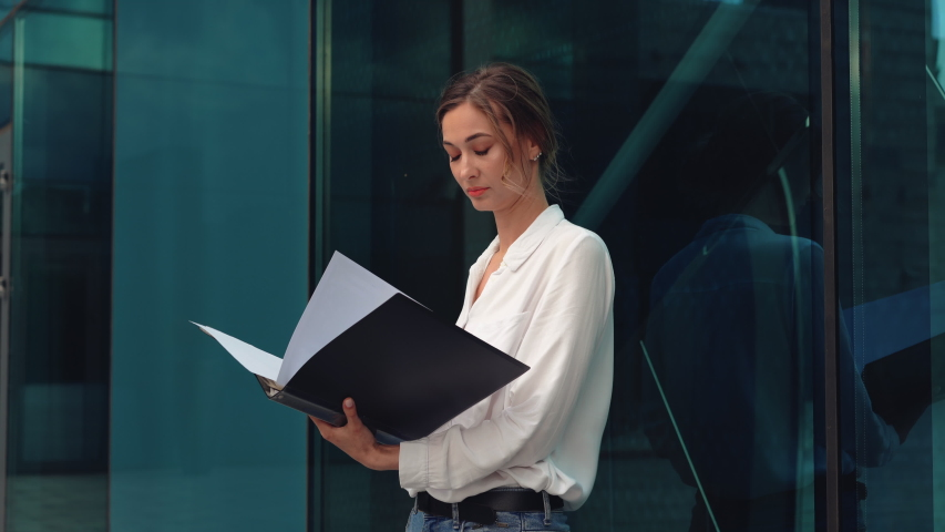 Businesswoman successful woman business person standing outdoor corporate building exterior Pensive elegance cute caucasian confidence professional business woman holding folder documents Bank worker | Shutterstock HD Video #1054414148