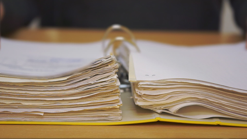 Open folder with documents. Entrepreneur studies financial documents. Hands holding fingers in page while reading | Shutterstock HD Video #1054414385