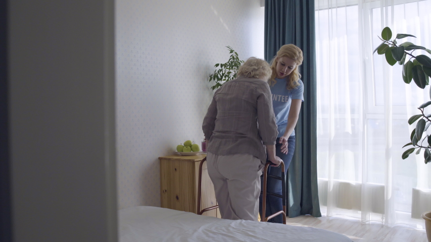 Volunteer girl helping old lady with walking frame, support for disabled seniors Royalty-Free Stock Footage #1054414766