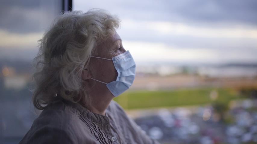 Senior woman wearing protective face mask, looking at city, epidemic lockdown Royalty-Free Stock Footage #1054414829