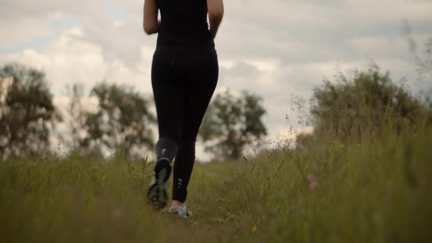 Triathlete Run After Triathlon Competition.Running Sport Recreation Workout.Fit Girl Cardio Training.Marathon Jogging On Trail.Runner Workout On Field.Half Marathon Endurance Jog.Running Legs And Foot Royalty-Free Stock Footage #1054414958