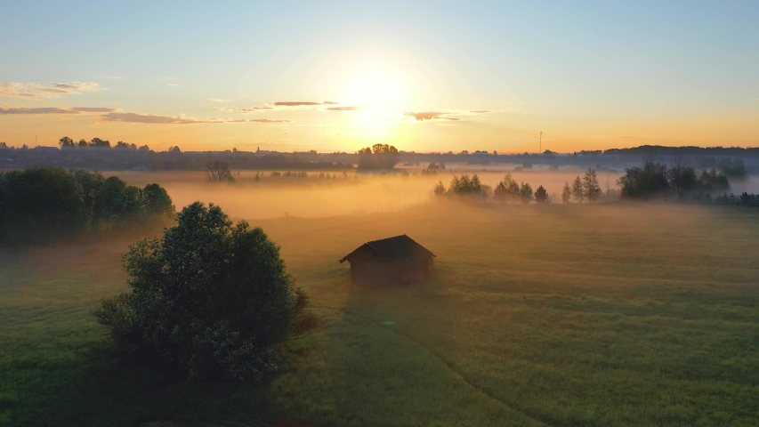 Fog morning over the plain and river floodplain of the meadow near a rural village with a house, aerial view landscape | Shutterstock HD Video #1054416710