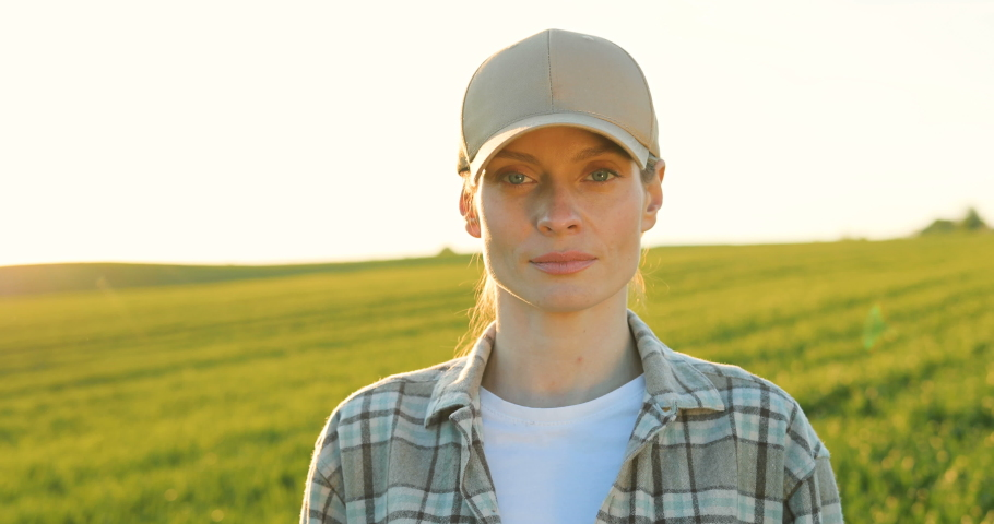 Portrait shot of attractive young Caucasian woman in hat standing in green field, smiling cheerfully to camera and giving thumb up. Female farmer with smile outdoors in summer. Camera zooming out. Royalty-Free Stock Footage #1054417151