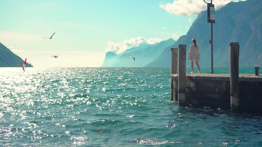 Blurred mysterious silhouette woman walks along pier. hair, dress flying wind, enjoy nature waves blue water. Back view. Seagulls fly over lake Lago di Garda sailboat floats. old town Riva Del Italy | Shutterstock HD Video #1054418117