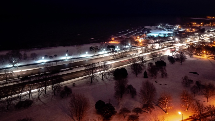 Beautiful zoom out aerial morning sunrise timelapse of the Chicago Lakefront along Lake Michigan with traffic flying by on Lake Shore Drive as night turns to day.