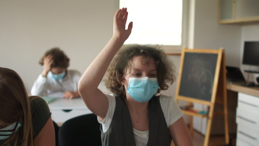 Curly masked schoolgirl pulls his hand up, ready to answer. Children in the class after quarantine coronavirus covid-19, back to school, post-quarantine life, new normality Royalty-Free Stock Footage #1054425383
