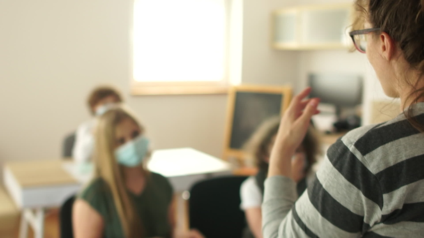The teacher in the classroom explains a new topic to students. Masked children, post-quarantine life, new normality after lockdown, coronavirus covid-19. Back to school Royalty-Free Stock Footage #1054425392