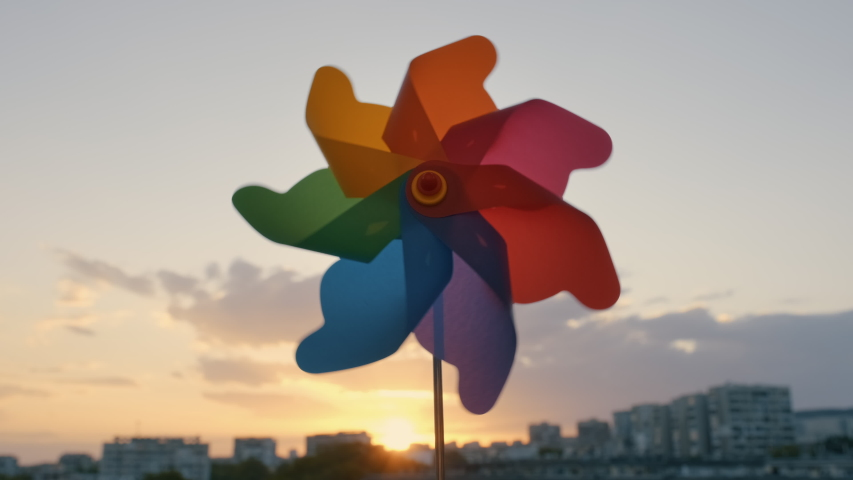 Pinwheel rotating colored plastic with blowing wind against a blue sky, white clouds, silhouettes of city buildings on sunset slow motion. Symbol of freedom and life. Toy spinner. Bright disk of sun Royalty-Free Stock Footage #1054425500