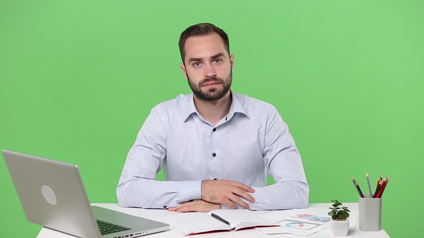 Young concerned business man in light shirt sit work desk pc laptop say hush be quiet with finger on lips shhh gesture isolated on green background studio Achievement business career lifestyle concept   Shutterstock HD Video #1054430030