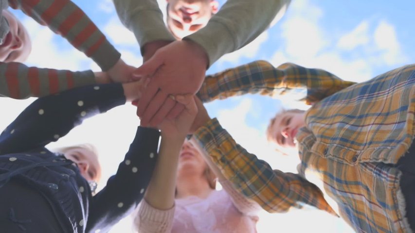 The concept of a friendly family. A large friendly family joins hands and diverges against the sky.