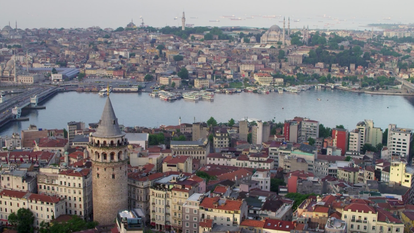 Aerial view of Galata Tower, Galata Bridge and Golden Horn (Halic) Metro Bridge in Istanbul City. Historic Peninsula, Beyoglu and Istanbul Bosphorus landscape. 4K Drone footage in Turkey.