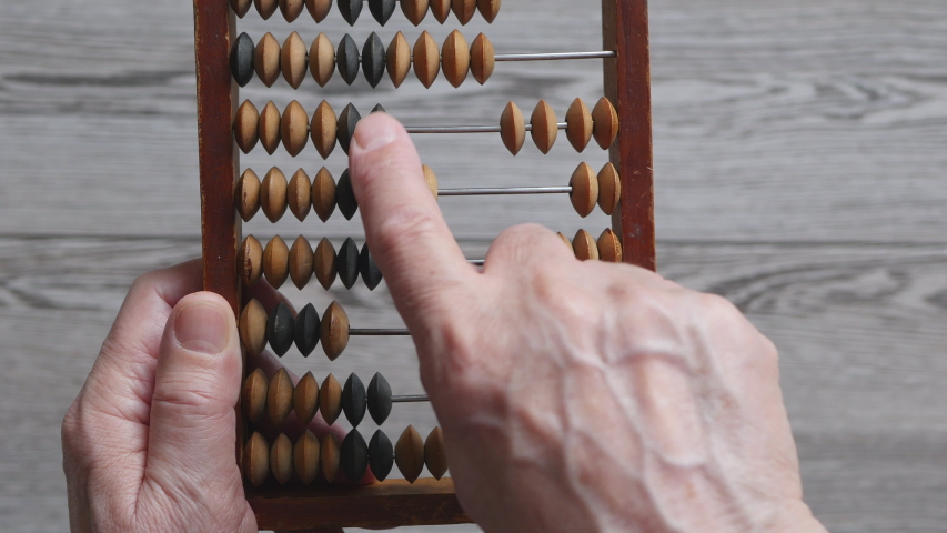 A Elderly Man Is Holding And Moves Wooden Knuckles On A Outdated Vintage Wooden Abacus On A Gray Background, Close-up. .