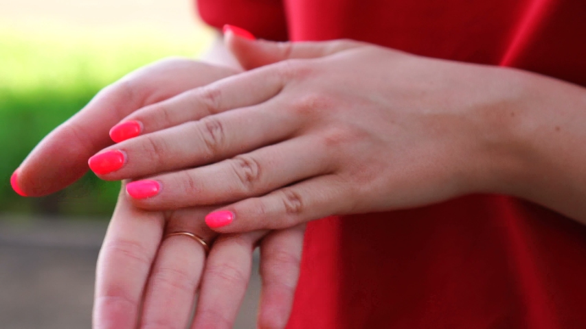 A close-up of a woman's hands rubbing sunblock, cream into the skin of her hands with gentle massage movements outdoors   Shutterstock HD Video #1054440599