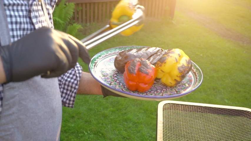 Hand of young man grilling vegetables on the barbecue plate with glowing coals, summer picnic time, bbq grill with fire in garden, vegan food and healthy eating outdoor fresh tasty food concept