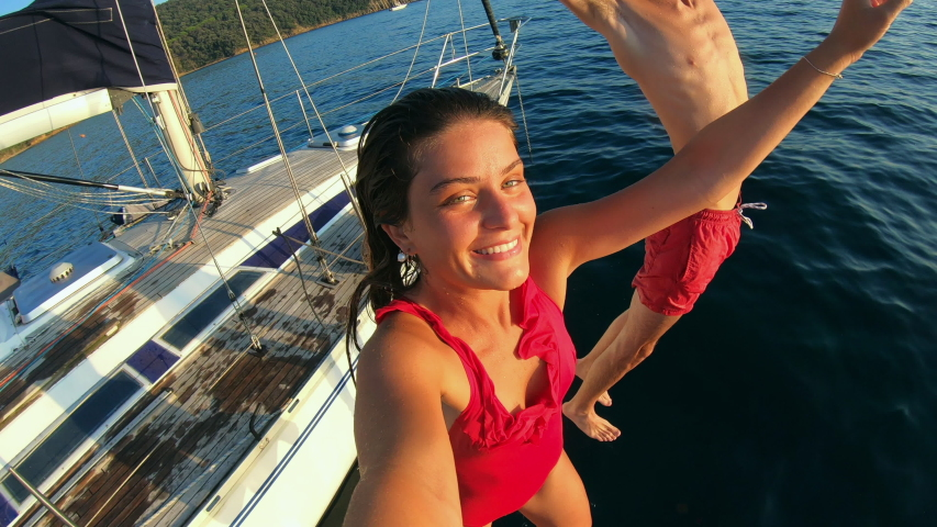 Young man and woman jumping off a sailboat in the Ligurian Sea.   Shutterstock HD Video #1054443398