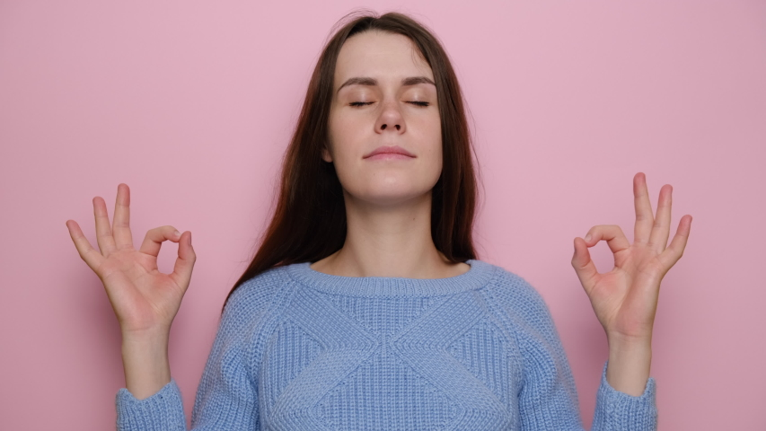 Cheerful young woman doing yoga exercise, wears sweater, cute girl meditating, standing over pink studio background closed eyes feels internal balance make fingers mudra gesture, no stress concept | Shutterstock HD Video #1054445036
