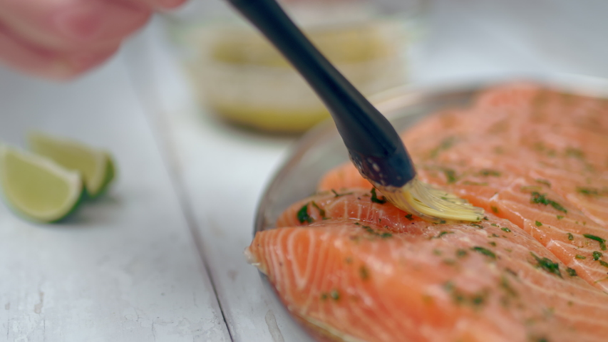 Close-up of brushing raw salmon with marinade sauce using a basting brush. Fillets of salmon being brushed with melted butter, garlic, greens. Concept of preparing salmon for cooking on the grill. Royalty-Free Stock Footage #1054447076